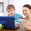 Happy couple paying by credit card in internet store  — Stock Photo