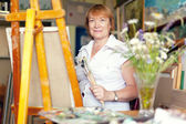 Woman artist paints the flowers on canvas — Stock Photo