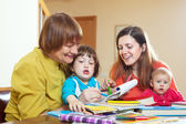 Happy grandmother with daughter and grandchildren drawing on pa — Stock Photo