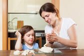 A girl with her mother learns to mold dough figurines in home — Stock Photo
