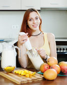 Ordinary young woman making beverages with blender from mango — Stock Photo