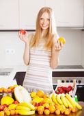Blonde long-haired woman with heap of ripe fruits — Stock Photo