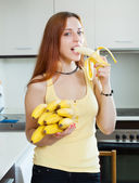 Long-haired woman eating banana — Stock Photo