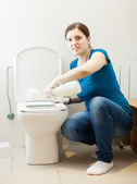 Woman cleaning toilet bowl with brush and cleaner — Stock Photo