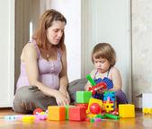 Zwangere moeder speelt met kind in huis — Stockfoto