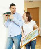 Middle-aged couple hanging the picture — Stockfoto