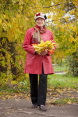 Woman in autumn with maple posy — Stock Photo