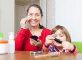 Mature woman with granddaughter doing makeup — Stock Photo