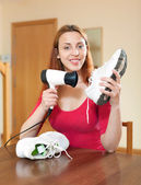 Happy red-haired housewife drying the running shoes with hair dr — Stock Photo