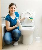 улыбаясь домохозяйка чистки унитаза с губкой — Стоковое фото