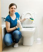 Smiling housewife cleaning toilet bowl with sponge — Stockfoto