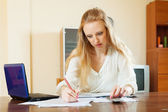 Ernstige blonde vrouw vult in documenten — Stockfoto