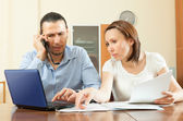 Couple calling by mobile about documents at home — Stock Photo