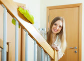 Smiling woman dusting stair railings — Stock Photo