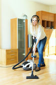 Happy long-haired woman in headphones cleaning with vacuum clean — Стоковое фото