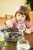 Two-years girl eats mussels — Stockfoto