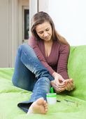 Beauty woman treats her toenails — Stock Photo
