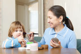 Mature woman putting facepowder on little girl — Stock Photo