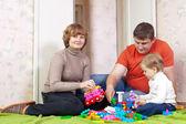родители и ребенок играет с детский конструктор — Стоковое фото