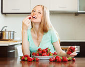 Long-haired woman eating strawberry in home — Stock Photo