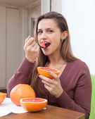 Girl eats grapefruit with spoon — Stock Photo