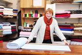 Saleswoman measures the fabric — Stock Photo