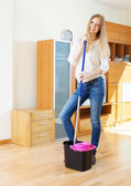 Cheeful ordinary woman washing parquet with mop — Stock Photo