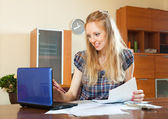Positive long-haired woman working with documents and laptop — Stock Photo