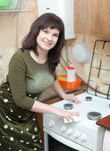 A dona de casa feliz limpa a fogão a gás — Foto Stock
