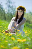 Happy girl sitting in dandelion meadow — Stock Photo