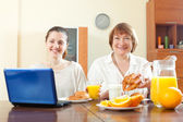 Women using laptop during breakfast — Stock Photo