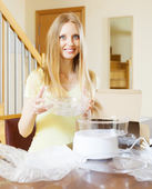 Blonde woman unpacking electric steamer — Stock Photo