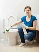 улыбаясь домохозяйка очистки туалет с губкой — Стоковое фото