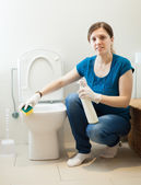 Smiling housewife cleaning toilet with sponge — Stockfoto