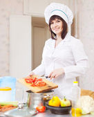 Cook with tomatoes on cutting board at kitchen — Stock Photo
