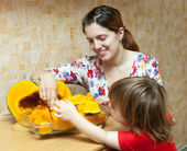 Happy mother with girl cooks pumpkinin — Stock Photo