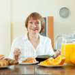Mature woman having breakfast — Stock Photo