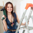 Sexy girl in dungarees with drill — Stock Photo