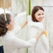 Shop assistant  helps to girl chooses fur cape — Stockfoto