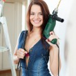 Stock Photo: Sexy girl in dungarees with drill