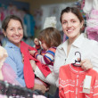 Two women and child at clothes store  — Stock Photo