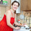 Housewife in red cleans the gas-stove — Stock Photo