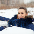 Girl in coat  lying down on the snow — ストック写真