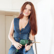 Stock Photo: Young woman in overalls with drill
