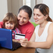 Family of three generations paying by credit card in internet st — Stock Photo
