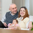 Happy mature man with wife and baby  — Stock Photo