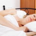 Blonde girl sleeping on white — Stock Photo