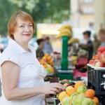Woman chooses fruits at market — Stock Photo #32306559