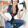 Woman in headphones with drill and hardhat — Stock Photo