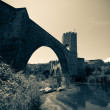 Medieval stone bridge over river. Imitation of old image — Stockfoto
